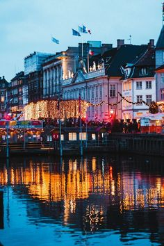 A nighttime shot of colourful houses and cute boats along the canal in Nyhavn, Copenhagen. Read this post to find out the best things to do in Copenhagen in winter, and how to see the best of the city in a weekend - the best restaurants, cafes, coffee shops, Christmas markets and architecture. #Copenhagen #Denmark #traveltips #Europe #travelguide