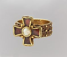 Finger Ring with a Cross.  Date: second half 5th–early 6th century Culture: Frankish Medium: Gold Dimensions: Overall: 5/8 x 13/16 in. (1.6 x 2.1 cm) bezel: 5/8 x 5/8 x 1/8 in. (1.6 x 1.6 x 0.3 cm) band: 13/16 x 1/4 in. (2 x 0.6 cm) Classification: Metalwork-Gold Credit Line: Gift of J. Pierpont Morgan, 1917 Accession Number: 17.192.229