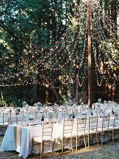 Utomhusmiljö, bröllopsdukning och dekoration med ljusslingor.