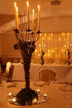 Woodland wedding table centres- Iron table candelabra dressed with ivy, moss and willow on a round mirror with clear votives, plus rustic lace and festoon backdrop by www.stressfreehire.com #venuetransformers. Perfect for barn venues.