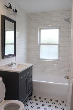 Farmhouse style bathroom remodel  |  White subway tile shower  |  Gray vanity  |  Black and white hexagon flower floor tile  | Chrome fixtures