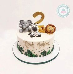 sweet African animal cake with gumpaste lion, zebra, and elephant toppers buttercream leaves and gold detailing Jungle Birthday Cakes, Animal Birthday Cakes, Baby Boy Birthday Cake, Boys 1st Birthday Cake, Jungle Theme Cakes, Jungle Safari Cake, Animal Cakes For Kids, Zoo Animal Cakes, Cake Minecraft