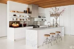 Author and photographer Kelly Klein's minimalist Palm Beach, Florida, kitchen features metal stools with rustic wood tops.