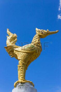 bird thai mythology: Tailandia estatua cisne de oro con ojos rojos sobre fondo de cielo azul. Golden Swan estatua de cemento en estilo tailandés.
