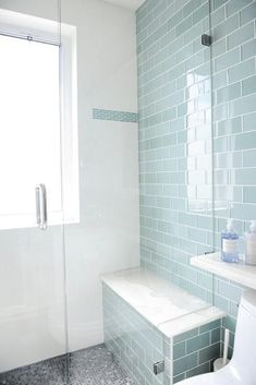 Full accent wall, or vertical stripe? Contemporary bathroom features a seamless glass walk in shower lined with blue glass subway shower tiles and a shower bench above the gray mosaic shower floor. Bathroom Floor Tiles, Bathroom Renos, Shower Floor, Bathroom Interior, Bathroom Ideas, Bathroom Gray, Bathroom Colors, Bathroom Renovations, Bathroom Wall