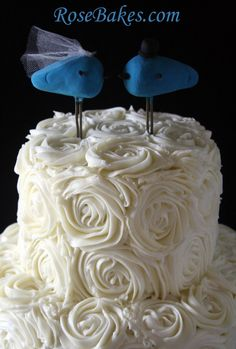 Blue Love Birds Topper on Buttercream Roses Wedding Cake by Rose Bakes featured at rosebakes.com   Just love the bluebirds on top of all the roses!