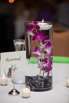 Place a purple gladiolus branch in a glass cylinder vase filled with water; with glass beads on the bottom and a floating candle -- centerpiece for guestbook table