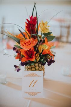 25 Lush And Bold Tropical Wedding Centerpieces a pineapple wedding centerpiece wih orange, red and yellow blooms and some greenery. Tropical Wedding Centerpieces, Wedding Flower Arrangements, Flower Centerpieces, Wedding Bouquets, Wedding Decorations, Wedding Crafts, Centerpiece Ideas, Tropical Wedding Reception, Tropical Weddings