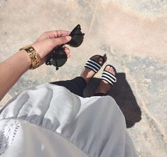 """Mais uma tendência dos anos 90 voltou com força total. A bolsa da vez são os chinelos Slides, principalmente o modelo da Adidas Adilette Slides. Eles são listradinhos de preto e branco e estão nos pés de várias fashionistas. Seguindo a linha da tendência """"normcore"""", onde ninguém mais liga para a moda e se veste como quiser priorizando sempre o conforto e a simplicidade. Esse modelo de chinelo combina com diversas roupas como salça, saias, shorts, vestidos, etc. É só deixar o visual mais no…"""