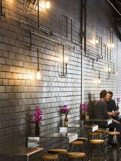 Original aplique de pared con tuberías y bombilla decorativa.