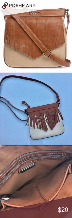 "Rosetti Cross-Body Fringe Handbag Tapered, chestnut fringe frames the front of this small but mighty bohemian mini crossbody bag. Crossbody strap, 24"" drop top zipper closure with knotted toggle synthetic; polyester lining bronze-tone metal hardware exterior back zipper pocket interior zipper pocket and 2 slip pockets 8½(H) x 9(W) x ¾""(D). Great condition! Bundle 2+ and save an extra 20%!💕 Price is firm! Rosetti Bags Crossbody Bags"