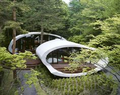 Situated within a dense thickness of trees the Shell House by Kotaro Ide of Artechnic unravels itself displaying its contrasting underbelly to the private audience of its owners. Brazen yet shy, the house's open form hidden within the trees presents an honest display of relevance to its situation. The curved forms synonymous with the outer shell of a snail or sea-faring crustacean stand on a plinth of wood creating the illusion that the form floats above the forest bed.
