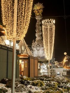 Snow-Covered Flowers, Christmas Decorations and Baroque Trinity Column at Christmas Market, Austria Photographic Print