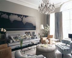 Fox-Nahem Associates designed this grand yet inviting living room in a Stanford White townhouse in Manhattan. An Ed Ruscha painting hangs over a custom sofa by Fox-Nahem. A pair of armless tufted chairs by Billy Haines and an 18th-century rock-crystal chandelier punctuate the space.
