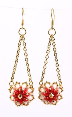 Segments of bright red and elegant ivory two-hole glass beads with sparkling gold seed beads in between and gold picots on the edges shaped as a two sides puffy flower are hanging on delicate gold color metal chains to a gold color metal ring. Gold color metal earring with a sophisticated gold Swarovski crystal in the middle.  Length: 2 7/8  Other color combinations are available upon request.  No shipping charges on all items in the store.