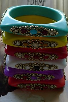 The bangle crafted in resin, featuring square shape design, carved detail to each side with gemstone embellishment.$15