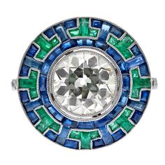 """Precision set sapphires and emeralds create a beautiful mosaic """"halo"""" surrounding the diamond center, allowing this engagement ring a truly unique and elegant display of color. Created in the Art Deco style, this ring exhibits wonderful symmetry and attention to detail."""