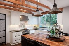 Exposed wood beams add a gorgeous touch to this farmhouse style kitchen. (: Genay Bell Interior Design) #interiordesign #kitchenremodel