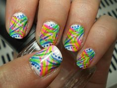 Today's Daily Nail Art is this colorful wispy nail design by Kaitlyan. It looks a bit complex but its actually much simpler than you might think to achieve. On a white base, alternate between blue and green nail art colors diagonally top right, and bottom left towards the center. With Pink and Yellow do the same on the opposite corners of the nails. Add in a few dots with blue and pink and seal it off with topcoat.