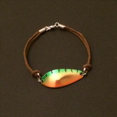 LuckyLures Fishing Bracelet uses a real fishing lure (spoon) on a brown leather cord strap.   Custom sizes and cord colours are available upon request for an additional $10. Contact seller for details.