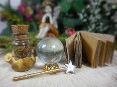 Miniature magic fairy kit with tiny silver and gold wand, 1 bottle of magic herbs, 1 crystal ball with iridescent rainbow effects, and 1 spell book.    Made of Metal, Clay, Glass, and Tree bark  Sold Individually or in a Set  Dimensions: Wand- Star is 10mm and 1 1/2 long Magic