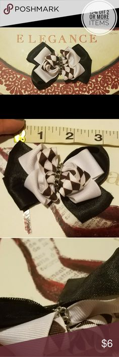Black & White Handmade Hair Bow with Chain This beautiful black and white hair bow is handmade.   Made of ribbon fabric and a metal chain.   Bow has some minor wear near the center of the bow from storage. Please reference the 3rd and 4th pictures as a reference.   Please see photos for current condition and measurements. Handmade Accessories Hair Accessories