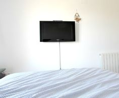 TV in the bedroom, white walls, blue striped bedding