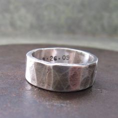 "a heavy band, formed from heavy silver sheet, just under a 1/4"" wide, the band has a hammered texture, heavy oxidation, and a matte finish"