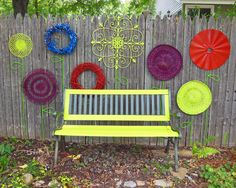 "Use round flat items (old wall hangings, wreaths, flattened iron pieces, or flat baskets, etc.). Paint bright colors to match your gardens color scheme. Hang on a fence wall as ""flower heads"" using nails, wire, or staples. Recycle an old electrical cord, hose, or wires into the stem and leaves – staple onto the fence. via Shawna Coronado"