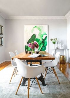 A palm art print serves as a backdrop for a rustic wooden table and Eames dining set.