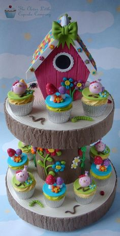 The cake stand is made from cake boards and cake dummies, all iced in sugarpaste to look like tree stumps, then decorated with cutesy flowers. The birdhouse is Rice Krispie treats, and the roof took aaaaages!!