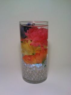 """Easter, Spring wedding, glass vase centerpiece, underwater light, pink, purple, yellow,orange. This glass vase has white glass beads with an underwater light. I used pink, purple, yellow and orange artificial flowers, and topped it off with a floating candle. This will look great as a bright, cheery Easter centerpiece, or for an indoor or outdoor Spring wedding.    The vase is about 7 1/2"""" tall.   http:www.etsy.com/shop/DeerwoodCreekGifts"""
