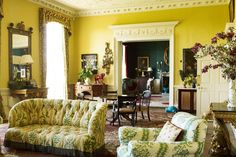 "[i]Yellow traditional-style sitting room with plasterwork ceiling and doorways. Floral carpets and sofas make for a brave pattern clash, maintaining the eccentric feel of the house.[/i]  Like this? Then you'll love  [link url=""http://www.houseandgarden.co.uk/interiors/furnishings/products/side-tables-console-tables-furniture""]Shopping: Side Tables[/link]"