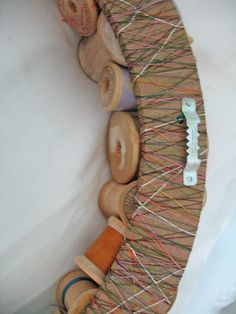 50 different sized wooden spools glued onto a wooden wreath frame. The frame is wrapped with different colored thread