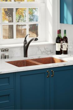 A stunning trifecta of winning colors. Navy cabinetry topped with marble countertops with a copper sink equals, perfection.