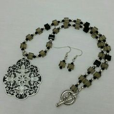 Handcrafted beaded necklace set This is a one of a kind handcrafted glass cube beaded necklace and matching earring set. The clear and black glass cubes are accented by Swarovski crystals and silver toned balls. An eye catching pendant finishes the piece. SORRY NO TRADES Jewelry Necklaces