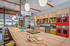 Add color to your kitchen with vibrant colorful appliances, cabinets, and open shelves as seen in Leslie Mackie's kitchen! Leslie Mackie owns Macrina Bakery & Cafe in Seattle and worked with Kerf Design on her kitchen.