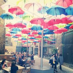 This beautiful place is Borough Market, London. There's a roof of coloured umbrellas.
