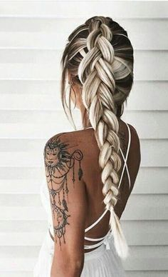 Fishtail hairstyle and arm tattoo