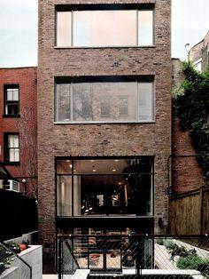 Fachada revestida com tijolinhos e janelas grandes