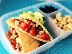 Wheat Pita with white bean mediterranean salad, cucumber slices, blueberries, and pistachios.