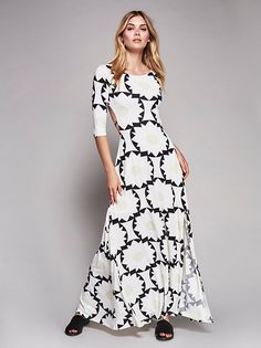 Featuring a modern print this American made maxi dress features a statement open back with single strap detailing. Rounded neck with three-quarter length sleeves and a slit detailing on the skirt.