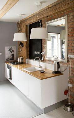 Zdjęcie: czerwona cegła,drewniane belki  i farba tablicowa na ścianie w białej kuchni z drewnianym blatem