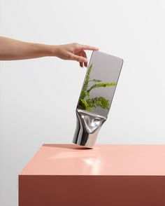London-based designer Philippe Malouin has created a freestanding mirror from a single metal cylinder that has been flattened and polished at one end.