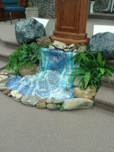 Alter for water coming out of the rock when Moses struck the rock . . . clear plastic, blue table cloth, rocks, greenery.