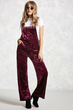 5ac16ae2b88 A pair of crushed velvet knit overalls featuring adjustable shoulder  straps
