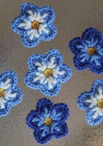 "I really like the look of these forgot-me-not flowers. not sure if the ""back circle (first row in blue)"" is necessary. Ill try it without. Free crochet pattern."