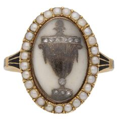Antique diamond and pearl 'urn' memorial ring. Ten round rose cut diamonds in silver cutdown settings decorating an intricate woven hair design forming an urn motif with white enamel background, surrounded by a row of 27 natural seed pearls in grain settings, flanked by trumpeted shoulders with black enamel motifs flowing down to a flat shank decorated with black enamel work, reading 'JANE.SAUNDERS.OB:26.JULY.1780:AE:27'. Tested yellow gold, circa 1780.