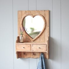 Wooden heart mirror with two convienient drawers. Oozing plenty of country charm with a distressed finish. Will make a practical addition to any home whether used in a bedroom bathroom or in a hallway for all the family Also has three wooden circular hooks to the underneath of the drawers