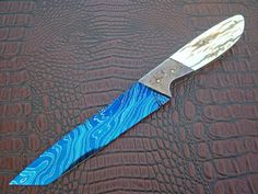 """Knifemaker Phil Ernest. This knife is huge in size.  It has a 6 3/4 inch blade and is 12 1.4 inches long. It is made of VERY thick Del Ealy Damascus steel. Bolsters are Damascus by Al May. A full 1/4"""" thick Mammoth Ivory Handles. Just AWESOME"""